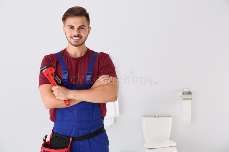 Młody człowiek z hydraulika wyrwaniem i toaletowym pucharem zdjęcie stock