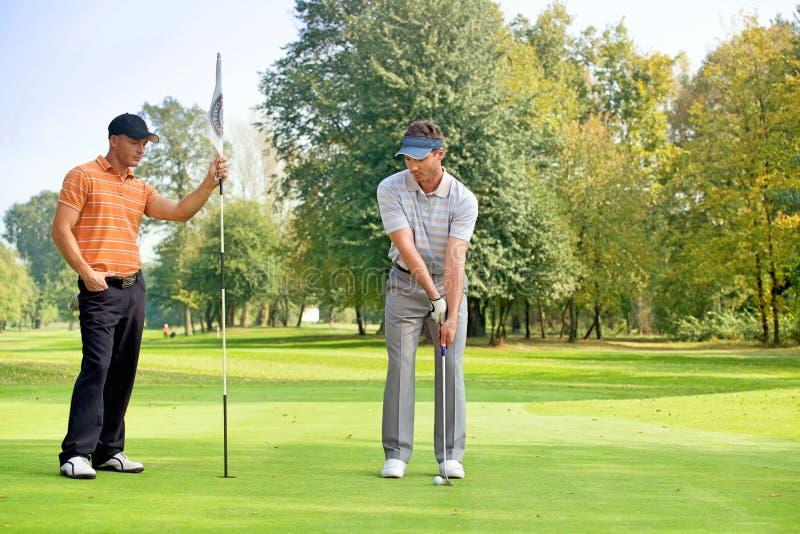 Młody człowiek z jego przyjacielem bawić się golfa w polu golfowym zdjęcia royalty free