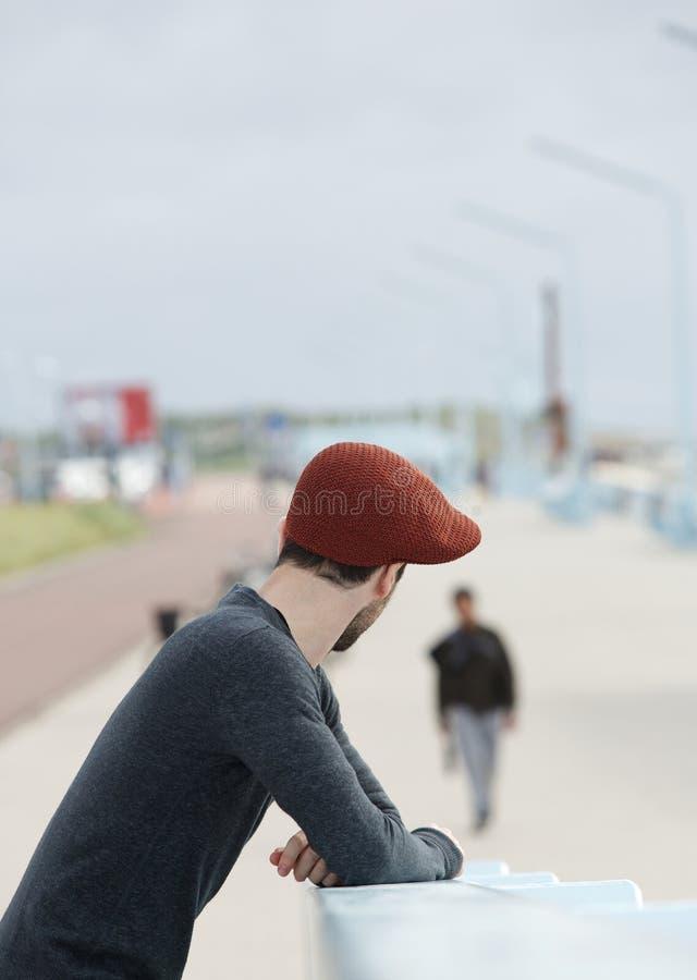 Młody człowiek z kapeluszową kręcenie głową zdjęcia stock