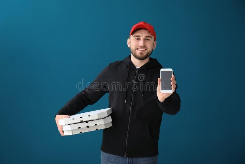 Młody człowiek z kartonowymi pizz pudełkami, telefonem komórkowym na koloru tle i Karmowa dor?czeniowa us?uga obrazy royalty free