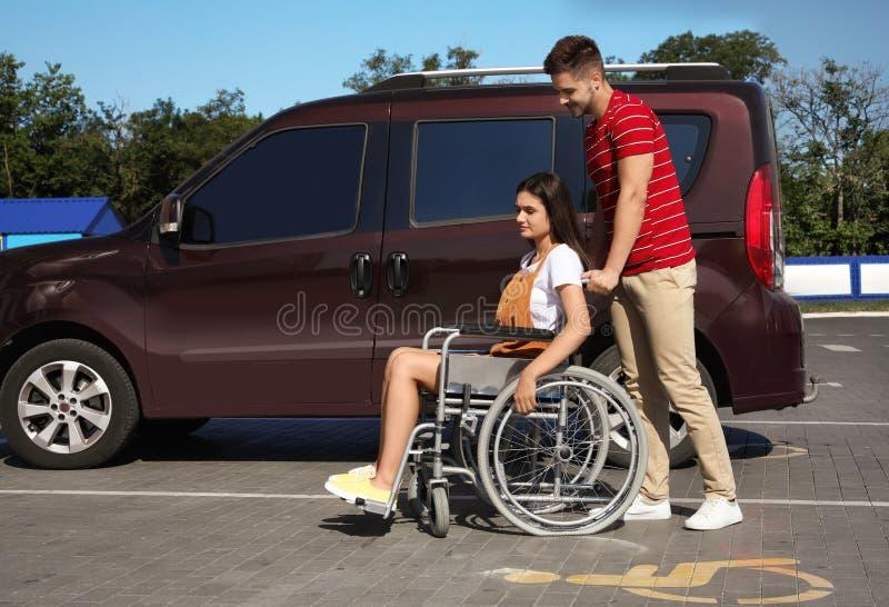 Młody człowiek z kobietą w pobliskim samochodzie dostawczym na samochodowym parking obrazy royalty free