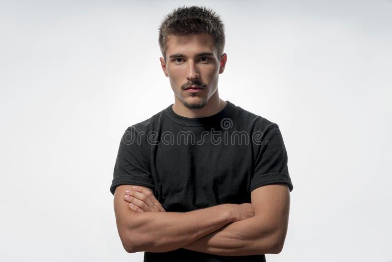 Młody człowiek z krzyżować rękami, odosobnionymi na bielu obraz stock