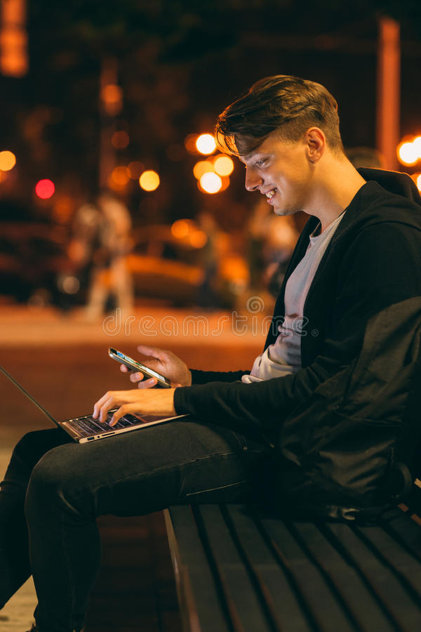 Młody człowiek z laptopem w nocy mieście zdjęcie royalty free