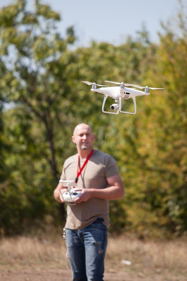 Młody człowiek z latającym trutniem w parku Mężczyzna z dalekim kontrolerem w jego wręcza brać powietrzne fotografie i wideo obrazy royalty free