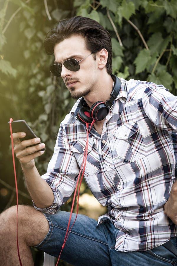 Młody człowiek z okularami przeciwsłonecznymi smartphone i hełmofonu plenerowym portem obrazy royalty free