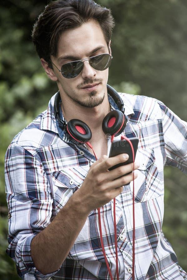 Młody człowiek z okularami przeciwsłonecznymi smartphone i hełmofonu plenerowym portem zdjęcia stock
