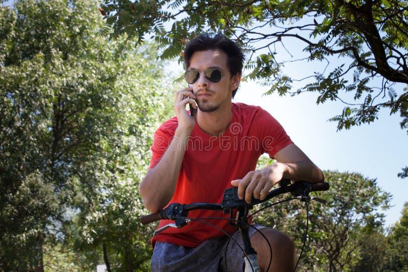 Młody człowiek z okulary przeciwsłoneczni use smartphone siedzi na rowerze w parku obrazy stock