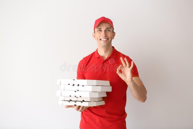 Młody człowiek z pizzą boksuje pokazywać OK znaka na lekkim tle Karmowa dor?czeniowa us?uga zdjęcia stock