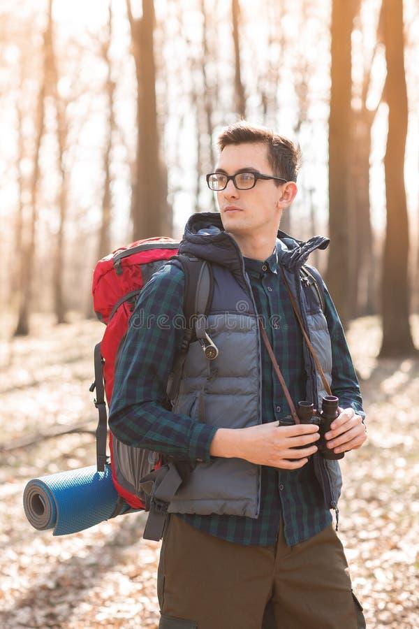 Młody człowiek z plecakiem z obuocznym w jego rękach i, wycieczkuje w lesie fotografia stock