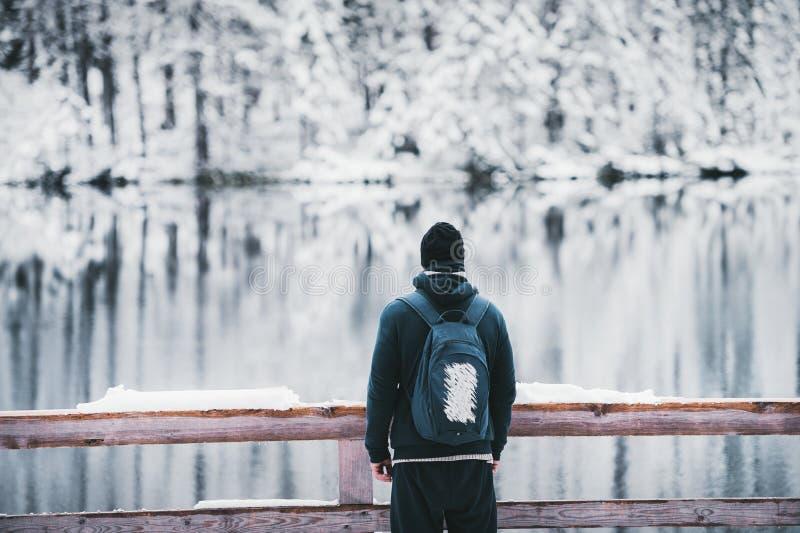 Młody człowiek z plecakiem podziwia malowniczego krajobraz zimy jezioro zdjęcia stock