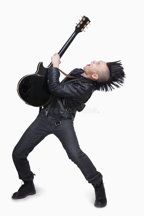 Młody człowiek z punkowym Mohawk bawić się gitarę fotografia royalty free