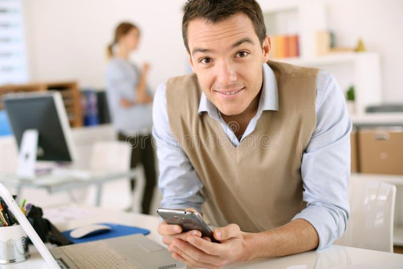 Młody człowiek z smartphone obsiadaniem w biurze zdjęcie stock