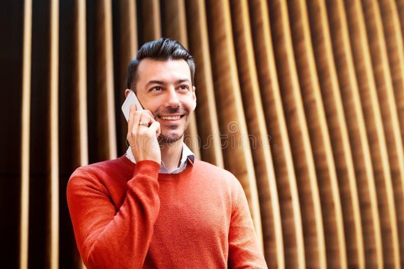 Młody człowiek z smartphone pozycją przeciw drewnianej ścianie obrazy royalty free