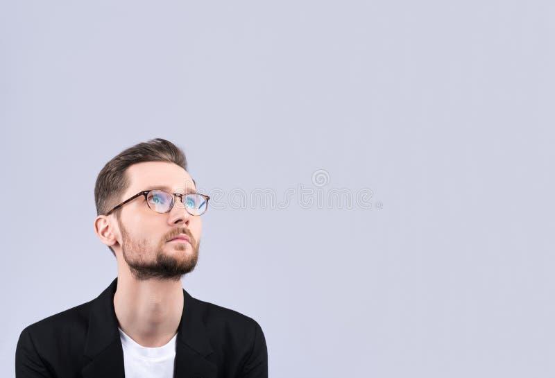 Młody człowiek z szkieł spojrzeniami blisko przy coś Myśleć ab zdjęcie royalty free