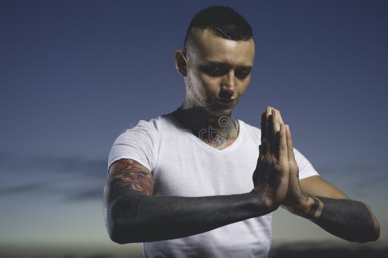 Młody człowiek z tattos medytuje joga i robi obraz royalty free