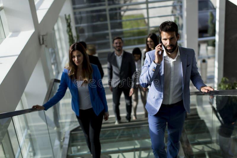 Młody człowiek z telefonem komórkowym na schodkach w nowożytnym biurze zdjęcie royalty free