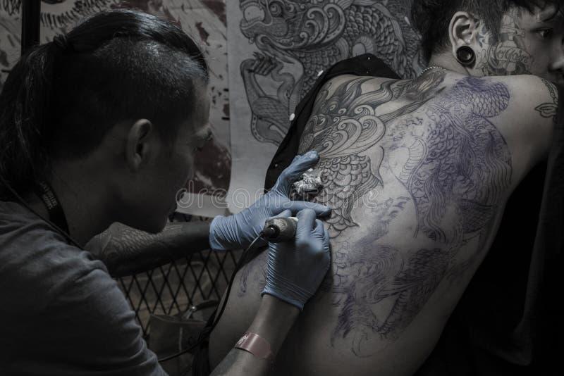 Młody człowiek z twarz tatuażem dostaje pełnego tylnego tatuaż Czarnej sztuki tatuażu studiiem przy Saigon tatuażu festiwalem 201 obrazy royalty free