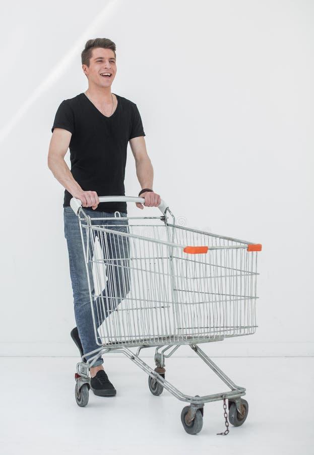 Młody człowiek z wózek na zakupy kroczy naprzód obraz stock