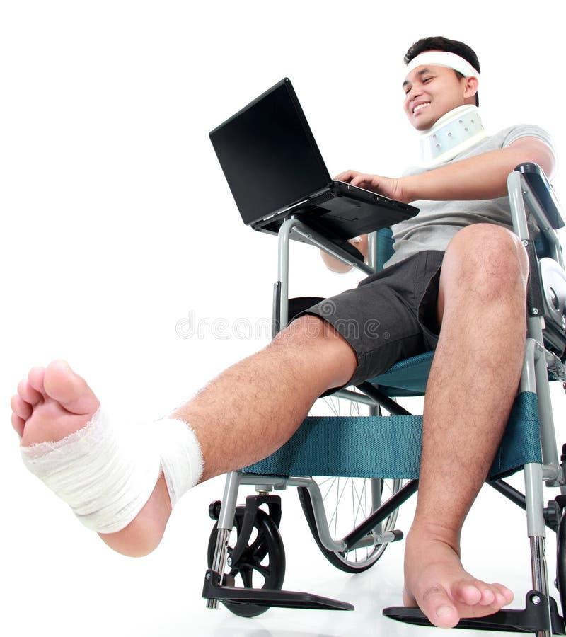 Młody człowiek z złamaną nogą w wózek inwalidzki pracie na jego laptopie obrazy stock