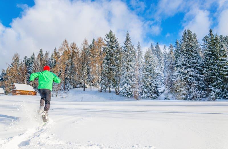 Młody człowiek z zielonej kurtki bieg w głębokim śniegu zdjęcie stock