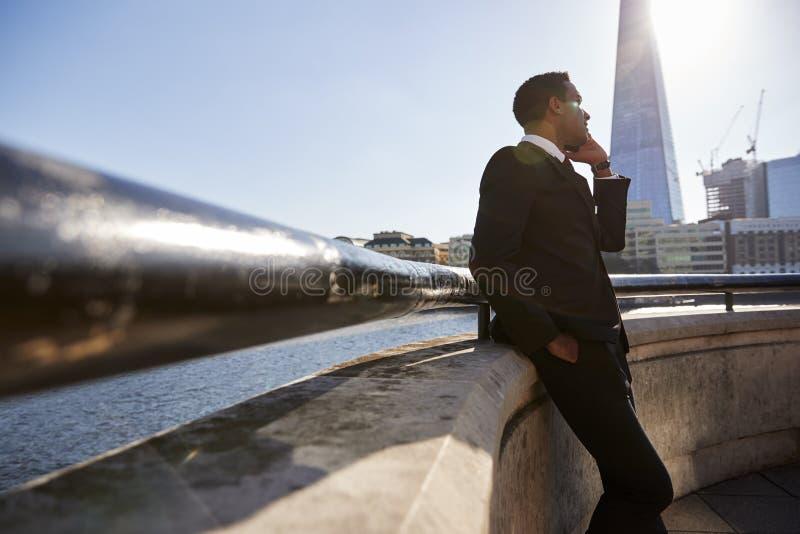 Młody czarny biznesmen jest ubranym kostium opiera na ścianie przy Thames bulwarem, Londyn, używać smartphone, niski kąt zdjęcia stock
