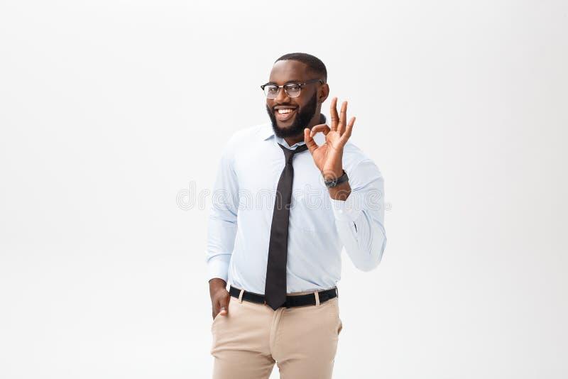 Młody czarny biznesmen ma szczęśliwego spojrzenie, ono uśmiecha się, gestykulować, pokazuje OK znaka Afrykański męski pokazuje ge obrazy royalty free