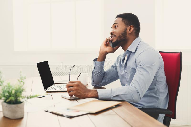 Młody czarny biznesmen opowiada na telefonie komórkowym zdjęcie stock