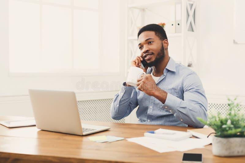 Młody czarny biznesmen opowiada na telefonie komórkowym zdjęcia stock