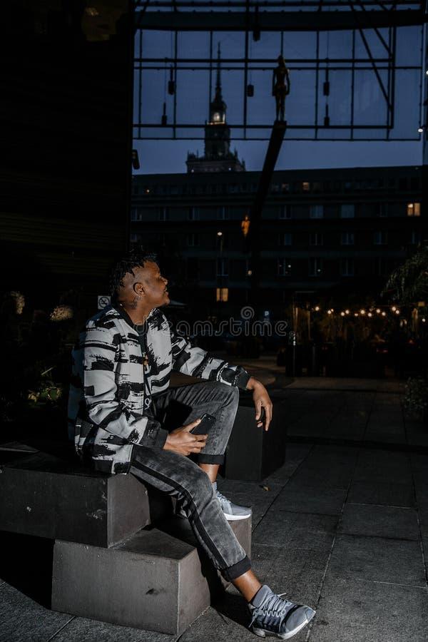 Młody czarny biznesmen opowiada na telefonie komórkowym i działaniu Szczęśliwy brodaty Afrykański biznesmen używa telefon Poj?cie obraz stock