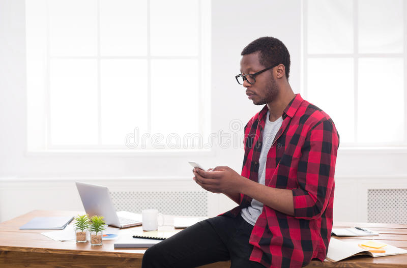 Młody czarny biznesmen robi rozmowie telefonicza na wiszącej ozdobie w nowożytnym białym biurze zdjęcia royalty free