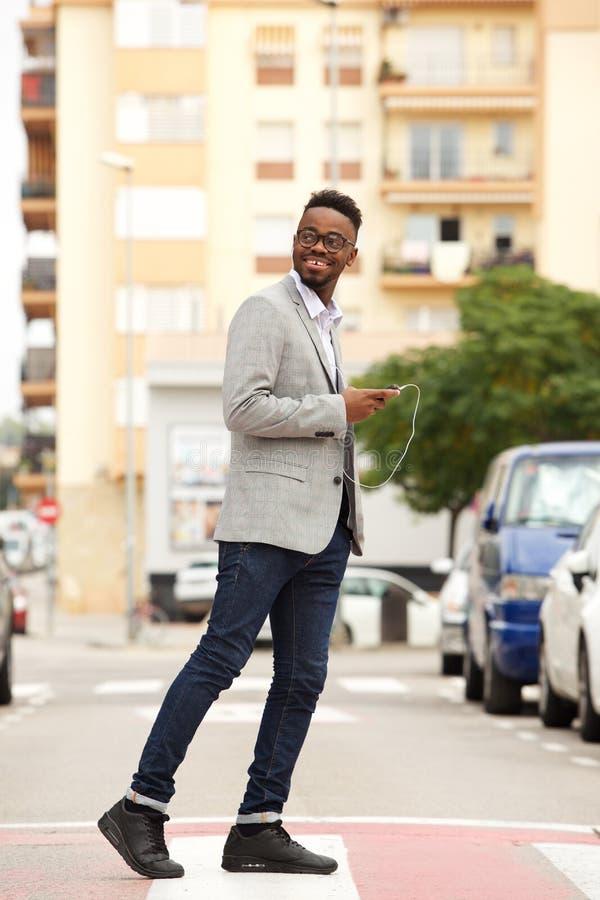 Młody czarny biznesmena odprowadzenie w mieście z telefonem komórkowym i słuchawkami obrazy royalty free