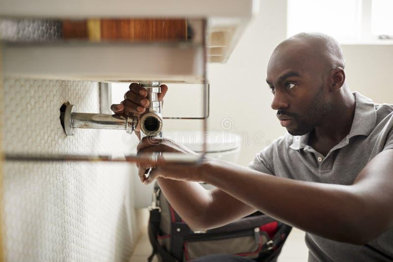Młody czarny męski hydraulika obsiadanie na podłogowym naprawianiu łazienka zlew, zakończenie w górę zdjęcia royalty free