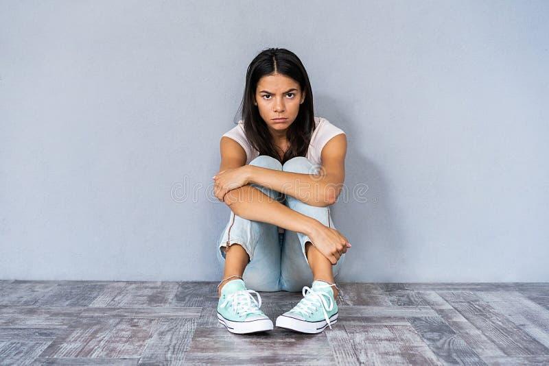 Młody depresji kobiety obsiadanie na podłoga obraz stock