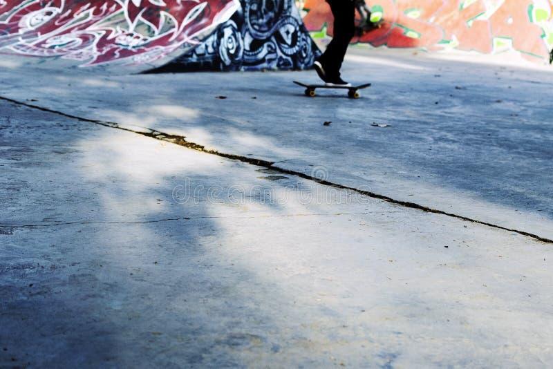 Młody deskorolkarza łyżwiarstwo wśrodku nowożytnego skatepark Deskorolka tło zdjęcia stock