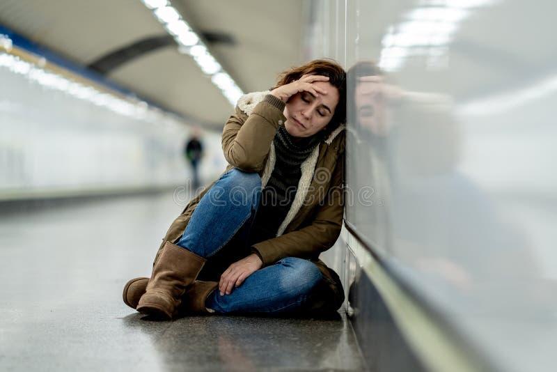 Młody desperacki dorosłej kobiety obsiadanie na ziemi na metra unde obrazy stock