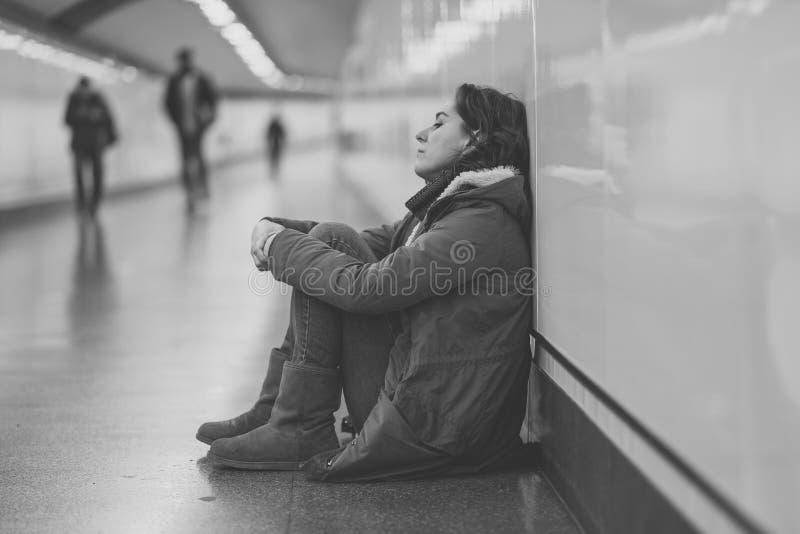 Młody desperacki dorosłej kobiety obsiadanie na ziemi na metra unde zdjęcie royalty free