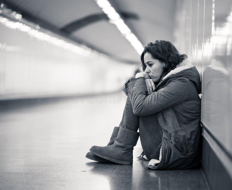 Młody desperacki dorosłej kobiety obsiadanie na ziemi na metra unde obraz stock