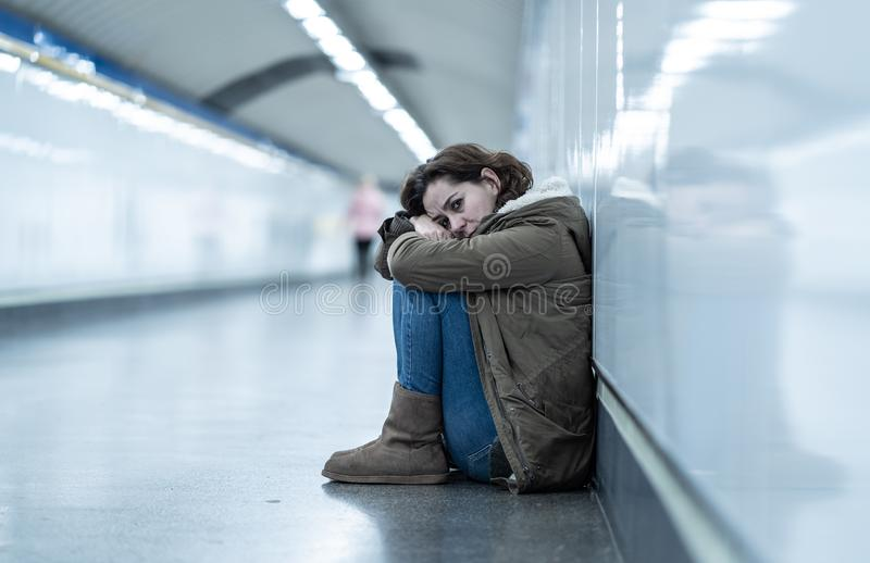 Młody desperacki dorosłej kobiety obsiadanie na ziemi na metra unde zdjęcie stock