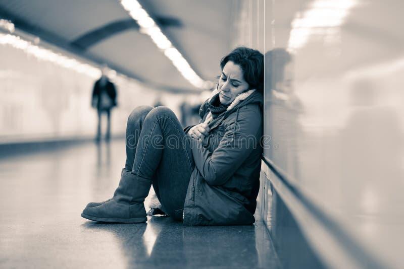 Młody desperacki dorosłej kobiety obsiadanie na ziemi na metra unde fotografia stock