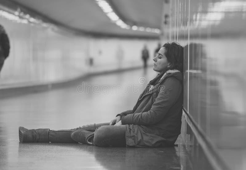 Młody desperacki dorosłej kobiety obsiadanie na ziemi na metra unde obraz royalty free