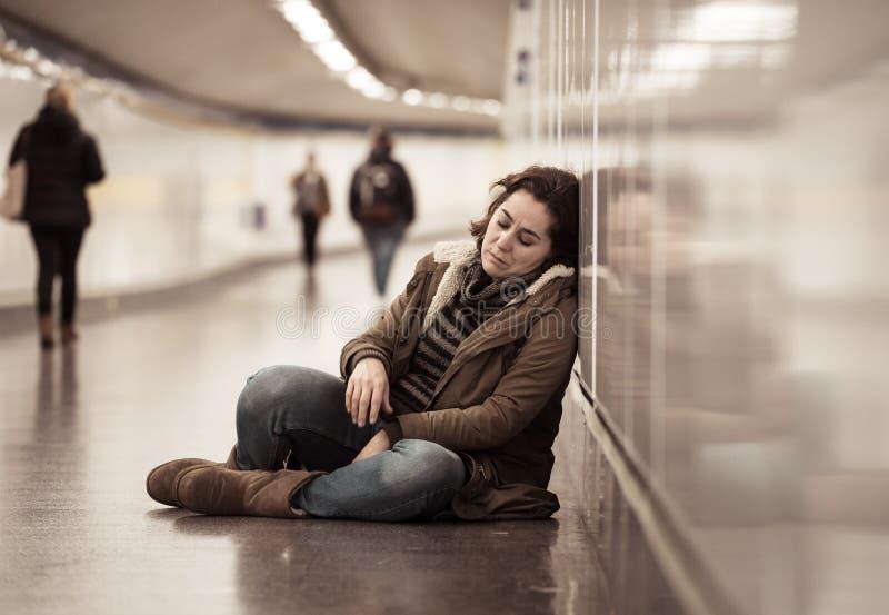 Młody desperacki dorosłej kobiety obsiadanie na ziemi na metra unde fotografia royalty free