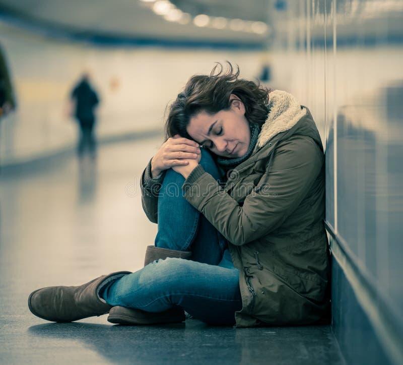 Młody desperacki dorosłej kobiety obsiadanie na ziemi na metra unde zdjęcia stock