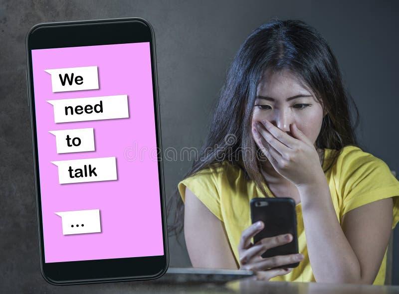 Młody desperacki i smutny Azjatycki Koreański kobiety uczucie deprymował ból złożonych z telefonem komórkowym online złamane serc zdjęcie stock