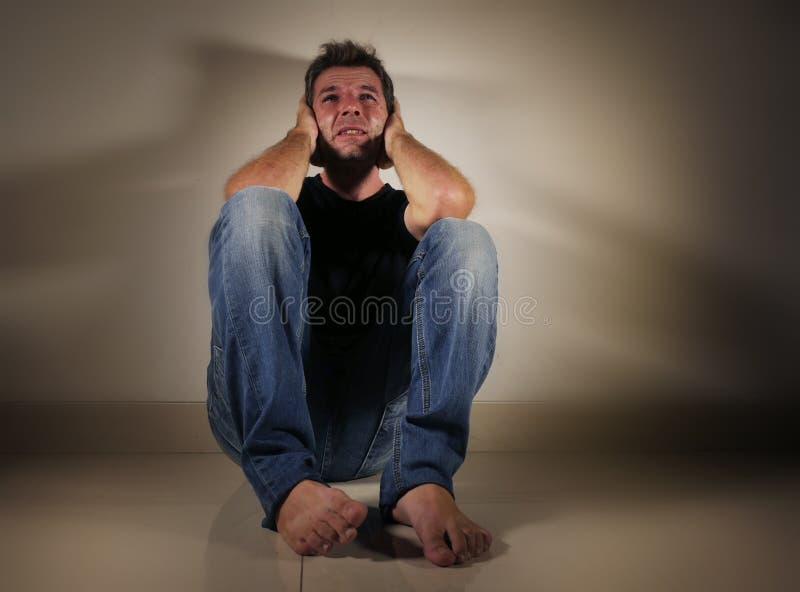 Młody desperacki, przygnębiony mężczyzna płacze samotnej obsiadanie podłoga patrzeje w studia świetle w domu i i obraz stock
