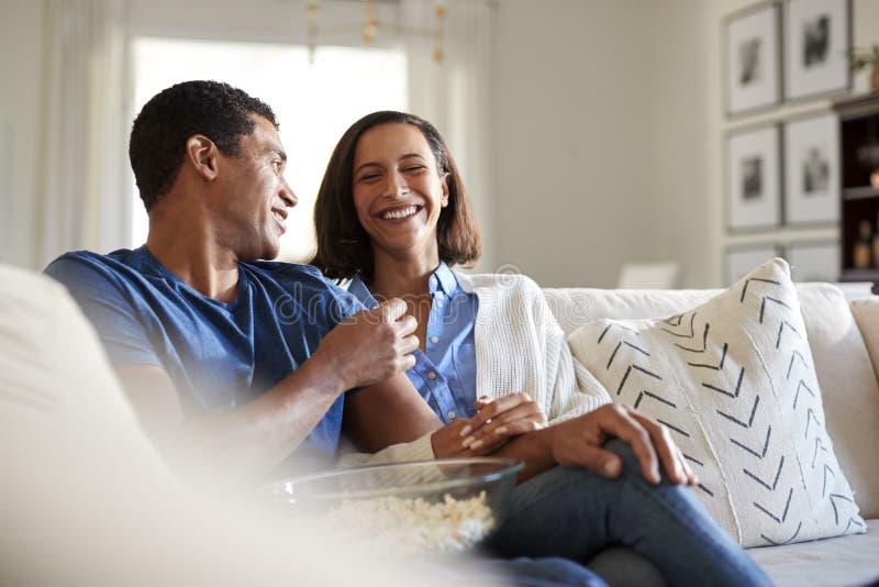 Młody dorosły amerykanin afrykańskiego pochodzenia pary obsiadanie na kanapie w ich żywym izbowym śmiać się i jeść popkornie, sel zdjęcie stock