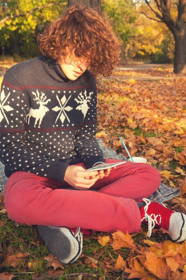 Młody dorosły mężczyzna obsiadanie w jesieni czytaniu i parku elektroniczna książka zdjęcia royalty free