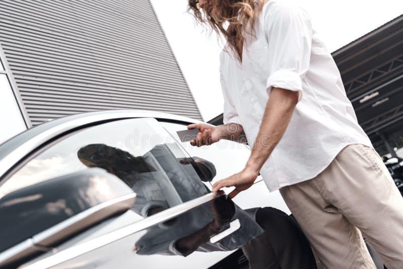 Młody dorosły mężczyzna stojący w pobliżu samochodu otwiera drzwi z kluczem elektrycznym obraz stock