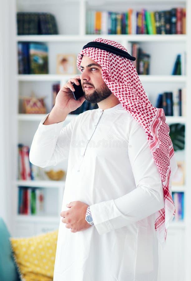 Młody dorosły muzułmański mężczyzna opowiada na telefonie w domu zdjęcie stock