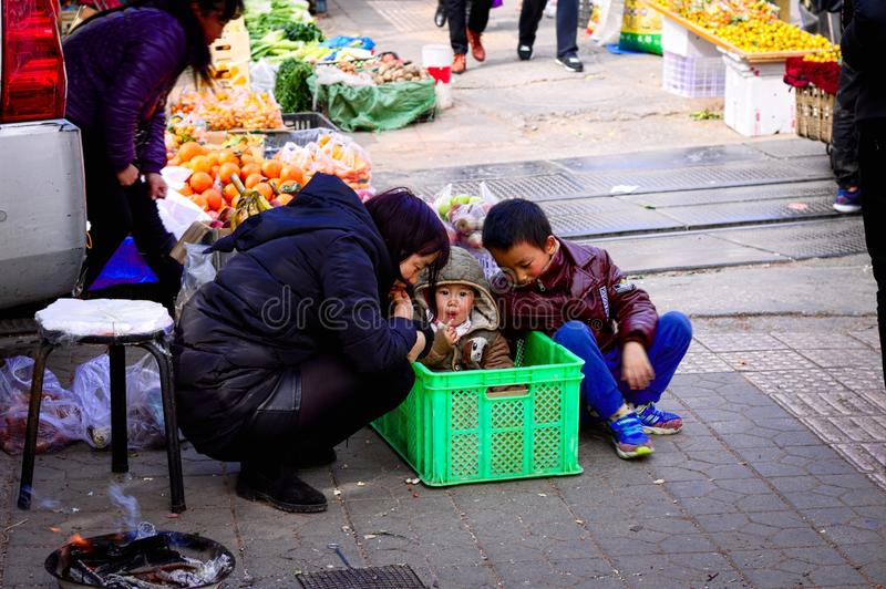 Młody dziecko w pudełku z jego mum i jego bratem - Uliczny rynek w Kunming obraz stock