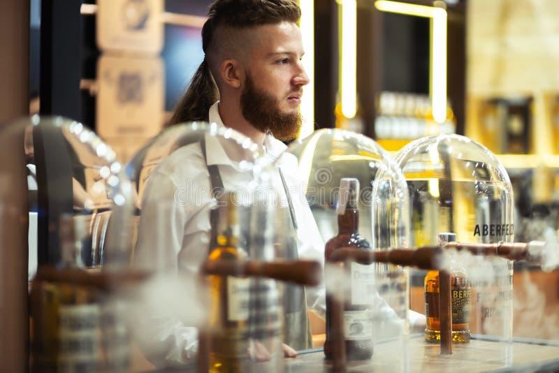 Młody elegancki barman na Dewar stojaku fotografia stock